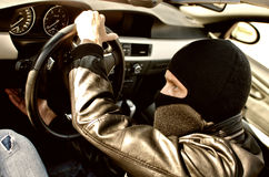 Bandit stealing a car. Bandit in mask stealing a car. Close up royalty free stock photography
