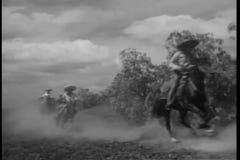 Banditen zu Pferd, die auf Schotterweg galoppieren stock video