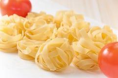 Bandnudeln (Nest) mit Tomaten Lizenzfreie Stockbilder