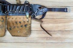Bandolera de cuero vieja de la caza en una tabla de madera Imagenes de archivo