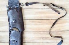 Bandolera de cuero vieja de la caza en una tabla de madera Foto de archivo libre de regalías