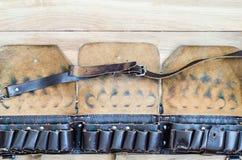 Bandolera de cuero vieja de la caza en una tabla de madera Imágenes de archivo libres de regalías