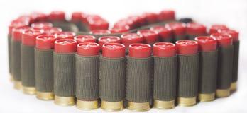 Bandolera torcida con los cartuchos rojos de la escopeta aislados Fotografía de archivo