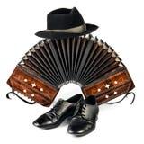 Bandoneon, tangoskor och en svart hatt som isoleras på vit Royaltyfri Foto