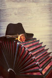 Bandoneon on wooden background with a male black hat on top. Text space. This image is toned Royalty Free Stock Image