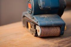 Bandschleifmaschine auf einer Holzoberfläche Lizenzfreies Stockbild