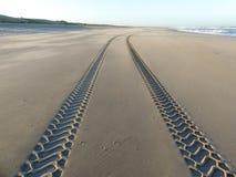 Bandsporen op vlot zandig verlaten strand royalty-vrije stock afbeeldingen
