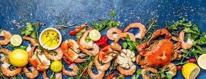 Baner Φρέσκα ακατέργαστα θαλασσινά - γαρίδες και καβούρια με τα χορτάρια και καρυκεύματα στο μπλε υπόβαθρο διάστημα αντιγράφων Στοκ Εικόνες
