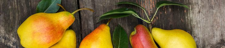 Baner av nya päron med sidor på den mörka lantliga trätabellen Arkivbild