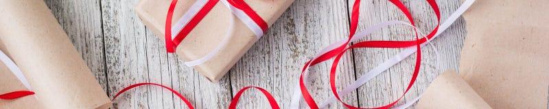 Baner av packande julklappar i kraft papper med röda och vita band royaltyfria foton