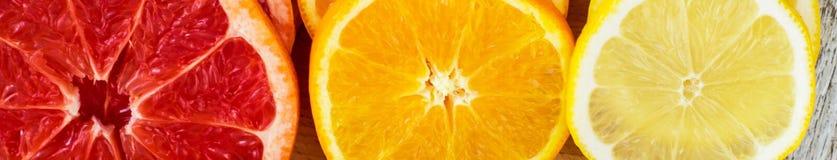 Baner av Sliced nya citroner, grapefrukter, apelsiner på en träskärbräda med en kniv Royaltyfria Foton