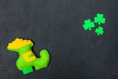 Baner för tema för dag för St Patrick ` s färgrikt horisontal Grön trollhand - gjord sko med guld- och treklöversidor på svart ba Royaltyfri Bild