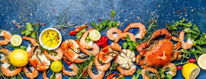 Baner. Fresh raw seafood - shrimps and crabs with herbs and spices on blue background. Copy space.  Stock Photo