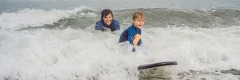 BANER, LÅNG FORMATfader eller instruktör som undervisar hans 5 den åriga sonen hur man surfar i havet på semester eller ferie arkivbild