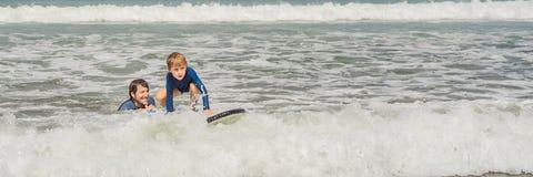BANER, LÅNG FORMATfader eller instruktör som undervisar hans 5 den åriga sonen hur man surfar i havet på semester eller ferie fotografering för bildbyråer