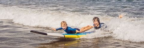 BANER, LÅNG FORMATfader eller instruktör som undervisar hans 5 den åriga sonen hur man surfar i havet på semester eller ferie royaltyfria foton