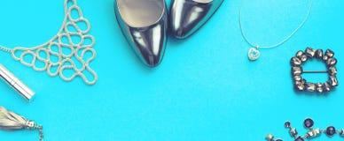 Baneruppsättningen av modetillbehör sänker lekmanna- färg för silver för smycken för skohandväskahalsband på blått utrymme för ko arkivbilder