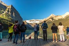Banff, Canadá - há 14o 2017 - grupo de turistas na frente da moraine do lago no amanhecer Céu azul, montanhas no backgr fotografia de stock royalty free