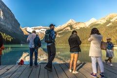 Banff, Canadá - há 14o 2017 - grupo de turistas na frente da moraine do lago no amanhecer Céu azul, montanhas no backgr foto de stock