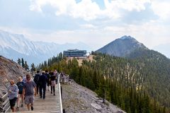 Sulphur Mountain in Canadian Rockies of Banff National Park. BANFF, CANADA - AUG 1, 2018: Visitors walk the wooden boardwalk on top of Sulphur Mountain between royalty free stock images
