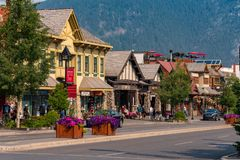 The  Banff Town Center, Canada. Banff, Canada--August 2, 2018.  The main shopping street in Banff with stores and shops and the mountains looming in the Royalty Free Stock Images