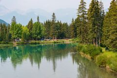 Small Park by Bow River. Banff, Canada--August 2, 2018. A small town park in Banff with the Bow River flowing past it Stock Images