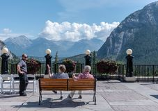 Tourists on a Bench in Banff. Banff, Canada -- August 5, 2018. Tourists staying at a luxury hotel in Banff are in conversation while seated on a bench facing the Stock Photos