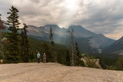 Tourists Overlooking Bow River Valley. Banff, Canada--August 3, 2018.  Wide angle shot of tourists standing on a ledge in Banff National Park with Mount Cirrus Stock Photography