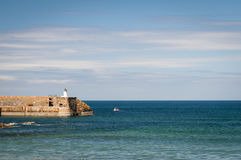 Banff lighthouse. Small boat leaving Banff harbour, Moray, Aberdeenshire, Scotland royalty free stock image