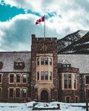 Banff National Park Administration Building. In Banff Alberta Canada. Canada flag in view in winter time stock images
