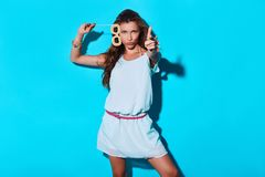 Bang!. Attractive young woman looking at camera and gesturing while standing against blue background royalty free stock image