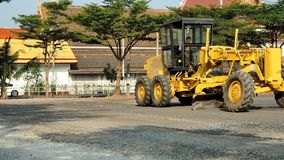 Modern three-axle road grader on gravel car park stock footage