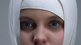 Bang gemaakt meisje die in headwrap camera, geweldslachtoffer, close-up bekijken stock videobeelden