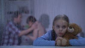Bang gemaakt meisje die teddybeer op regenachtige dag, het luisteren oudersruzie koesteren stock videobeelden