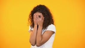 Bang gemaakte biracial vrouw het letten op verschrikkingsfilm, sluitend gezicht met handen, vrees stock footage