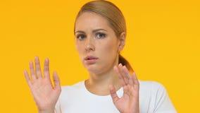 Bang gemaakte vrouw die tegen vreemdeling tegen oranje achtergrond, close-up beschermen stock video