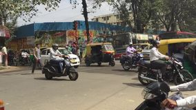 Bangalore, India - 30 JAN 2017: A street and traffic scene from the side of a busy road in Bangalore, India, with tuk. Tuks, cars and motorcycles making their stock footage