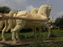 Bangalore, Karnataka, Indien - 1. Januar 2009 gelbe Farbstatue von den Pferden befestigt zu einem Kampfwagen Stockfotografie