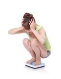 Bange jonge vrouw op schaal Stock Foto's