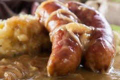 Bangers e erva-benta Salsicha cozida no molho de cebola imagem de stock