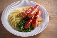 Bangers en Brij Worsten, fijngestampte aardappel, groene erwten en gebraden ui op witte plaat op houten lijst stock afbeeldingen