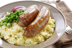 Bangers and Mash. Sausages over mashed potato with seeded mustard, and peas Royalty Free Stock Images