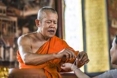 Bangkog, Tailândia, o 4 de março de 2016: Monge que tieding acima de uma linha santamente em uma mão no templo Imagens de Stock Royalty Free
