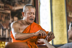 Bangkog, Thailand, March 4, 2016: Monk tieding up a holy thread on a hand in the temple.  Royalty Free Stock Images