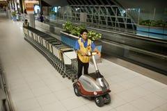 Bangkok airport. BANGKOK – JANUARY 17. Airport staff moving trolleys in early morning Bangkok airport on January 17, 2012. Suvarnabhumi airport is world's 4th Stock Images