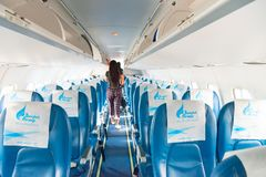 Bangkok airways airplane interior. PHUKET, THAILAND - 24 APR 2017: Bangkok airways airplane interior with leaving passengers on background Royalty Free Stock Photo