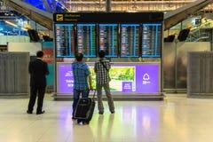 BANGKOK - 4. April Passagiere, die den Flugplan auf Flughafendiagrammen an Suvarnabhumi-Flughafen, am 4. April 2014 in Bangkok üb Lizenzfreie Stockbilder