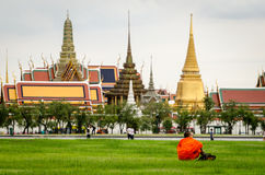 Bangkok, Bhuddist monk sitting in Sanam Luang park with Wat Phra Kaeo Stock Photos
