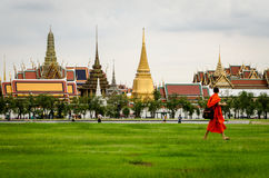 Bangkok, Bhuddist monk walking in Sanam Luang park with Wat Phra Kaeo Stock Photo