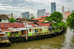 Bangkok channel and constrast between poor and rich houses. Bangkok channel and skyline with constrast between poor and rich houses royalty free stock images